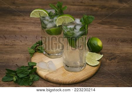 summer drink mojito, mohito with mint, ice and lime, in glasses, on a wooden table, macro photography