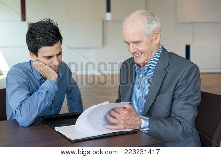 Pleased senior man showing report to accountant while they discussing business strategy. Concentrated young male specialist examining business papers with boss. Development concept