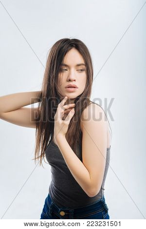 Do not like. Attractive wistful energetic woman placing hand behind head while gazing aside and touching her chin