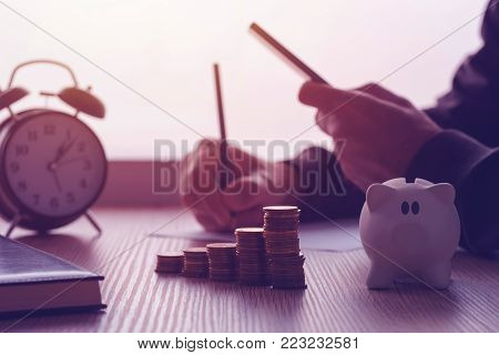 Savings, finances, economy and home budget calculations. Close up of man doing calculations and writing notes at home.