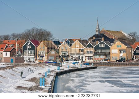 Winter landscape Dutch fishing village Urk with frozen harbor covered with snow