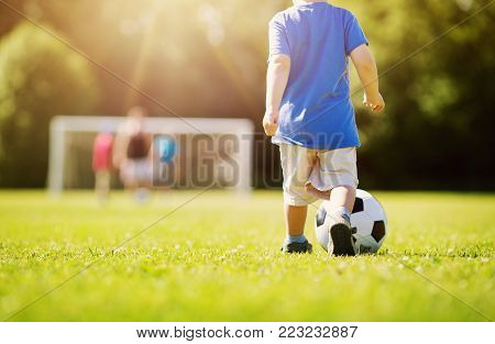 Little boy playting football on the field with gates. Active child in summer with ball