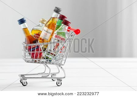 Minsk, Belarus - January 16, 2018: Illustrative editorial photo of mini shopping cart full of small alcohol bottles - Jameson whiskey, Camus and Martell cognacs, Havana club rum, Beefeater gin. Minsk, Belarus.