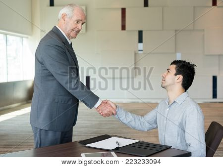 Young managing director talking to senior employee and shaking his hand after signing agreement. Pleased businessman happy about meeting with new partner. Trust and stability concept