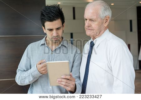 Two concerned office employees looking at sale report on tablet screen. Senior CEO and young manager calculating loss. Business meeting and failure concept poster