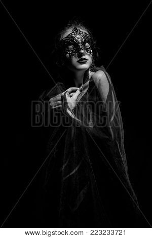 Beautiful young girl wrapped in transparent shawl with painted body and black mask on her face stands against black background. Body art. Black and white image.