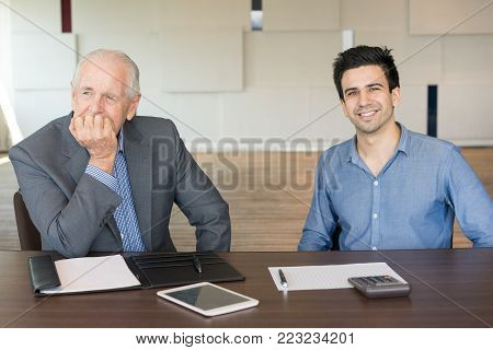 Sad senior man in suit and smiling young office worker in meeting hall. Senior executive stepping aside for young employee. Business meeting and retirement concept