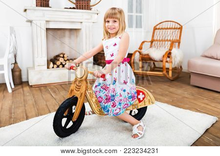 Happy smiling little girl riding a wooden runbike at home in the living room