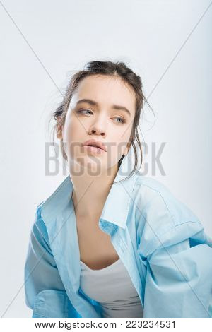 So unfair. Desperate attractive young woman lowering shoulder while looking aside and dressing in male shirt