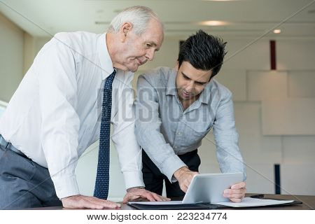 Two serious business people looking at tablet screen. Manager holding presentation on tablet for executive and pointing at screen. Business meeting and presentation concept