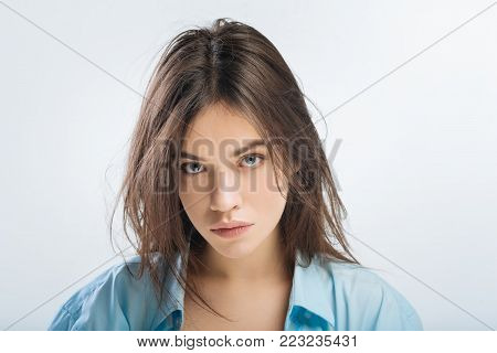 Bad dream. Unsatisfied displeased young woman posing on the isolated background while asking questions and staring at the camera