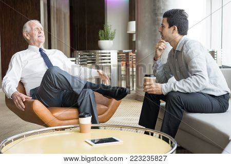 Two business people drinking coffee and conversing in office lounge. Young journalist interviewing successful business owner in white shirt and tie. Business meeting and success concept