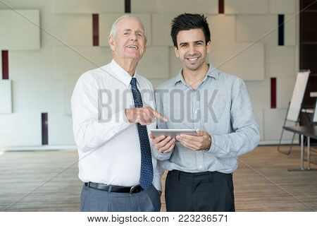 Senior and junior office employees smiling at camera and pointing at tablet screen. CEO and manager calculating profit. Business meeting and success concept