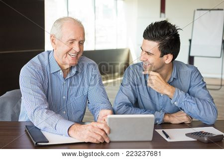 Two positive business people discussing work issues. Senior legal adviser pointing at tablet and consulting young entrepreneur. Business meeting and consulting concept