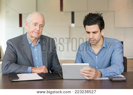 Distrustful senior man in suit looking at tablet screen while serious young man using device. Startuper holding presentation for investor. Business meeting and negotiation concept