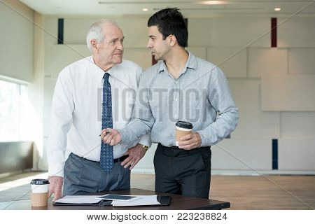 Young manager offering pen to upset senior employee for signing document. Business owner firing senior executive. Employee pushing his idea to skeptical boss. Business and communication concept.