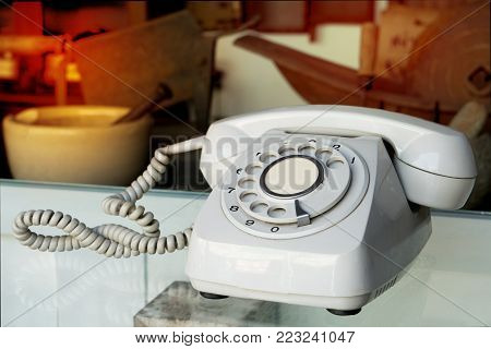 Close up of vintage rotary telephone on table. Vintage rotary landline telephone or wire telephone for contact us concept focus on dialpad.