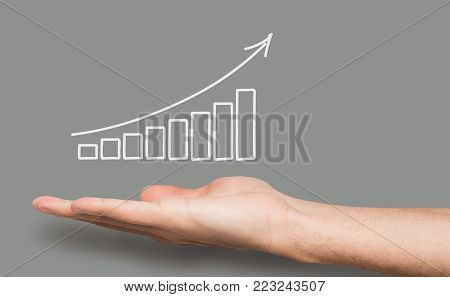 Conceptual business success background. Caucasian male hand over gray backdrop with growth graph. Revenue, financial well-being and achievenment concept, copy space