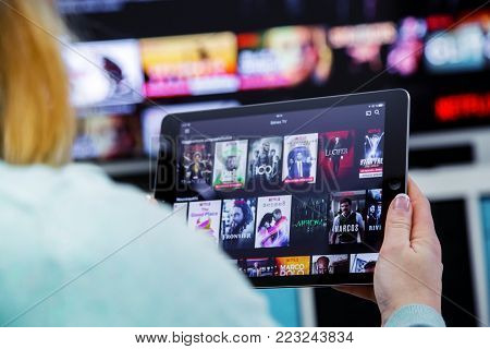 Benon, France - January 21, 2018: Woman Holding A Touch Pad And Switching Channels On France Netflix