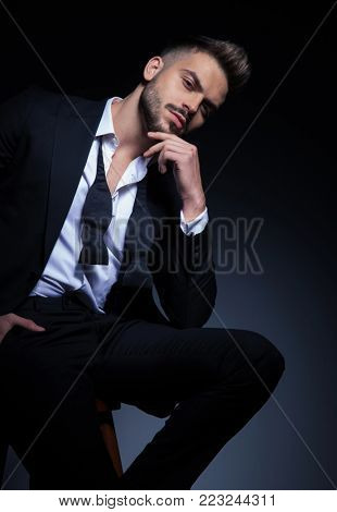 arrogant elegant man in tuxedo holding hand on chin while sitting on a stool in studio