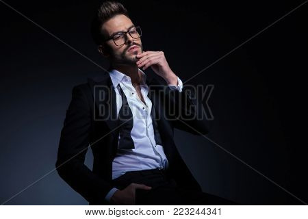 thoughtful young elegant man in tuxedo with undone bowtie sitting in studio
