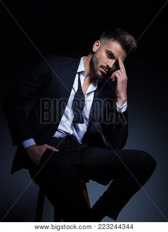 cool elegant man in tuxedo having a headache , he sits on a chair with hand in pocket and fingers on forehead; modern pensive young man  poster