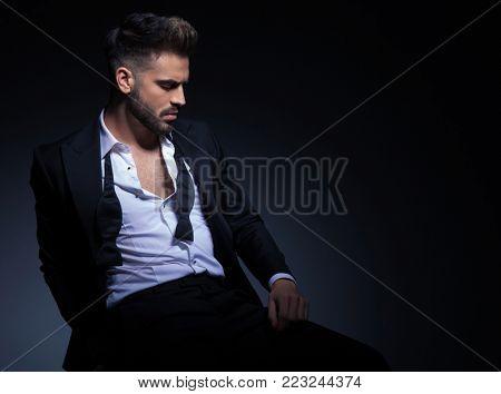sad elegant young man in tuxedo resting on a chiar in studio