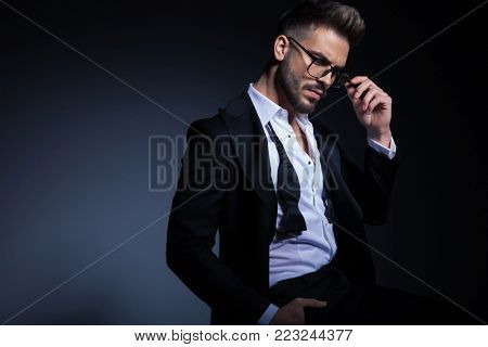side view of a seated elegant man in tuxedo and undone bowtie fixing glasses  on grey studio background