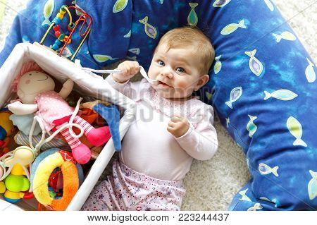 Adorable baby girl playing with educational toys in nursery. Happy healthy child having fun with colorful different toys at home. Cute baby learning grab and hold things and toys, sitting and crawling
