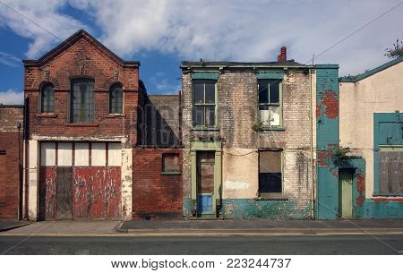 derelict houses and abandone garage on a residential street with boarded up windows and decaying crumbling walls