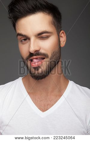 flirty young man sticking out his tongue and winks on grey background