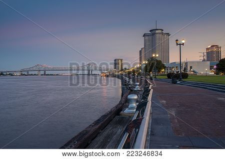 New Orleans, Louisiana - June 17, 2014: View of the Mississippi river from the city of New Orleans riverfront, with the Great New Orleans Bridge on the background in New Orleans, Louisiana, at dusk.