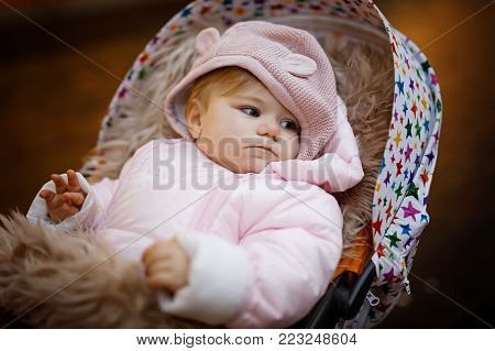 Cute little beautiful baby girl sitting in the pram or stroller on winter evening on christmas market. Happy smiling child in warm clothes, fashion stylish baby overall.