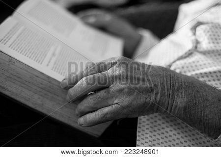 Close up of old man's hands holding book in his lap. Reading literature and continuous learning in 80s. Black and white image technique