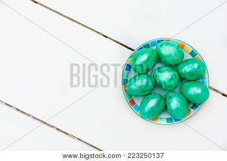 Easter eggs on wooden background. Colorful eggs in different colors - red, yellow, orange, purple and green. Old tradition for holiday. Close-up of many eggs