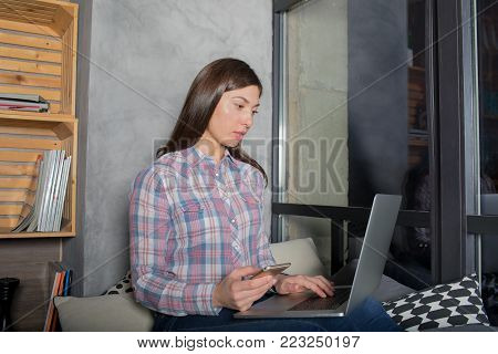 Woman content manager or writer working distance on laptop computer, sitting on a windowsill in home or co-working. Female clever freelancer using mobile phone and net-book for search information