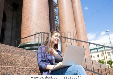 Young smart woman student learning on-line via laptop computer, sitting outdoors on the steps of the University. Hipster girl keyboarding on net-book resting near college or architectural building