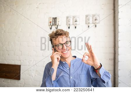Young smiling businessman showing fingers okey while talking on mobile phone. Happy hipster guy having cell telephone conversation looking in camera while sitting in coffee shop or office space