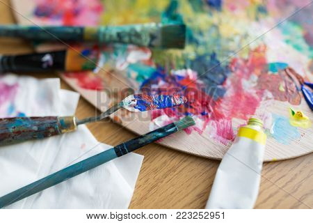 fine art, creativity and artistic tools concept - close up of palette knife or painting spatula, brushes and paint tube