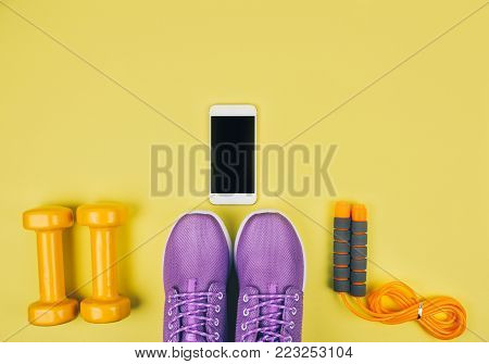 Flat lay shot of sneakers, dumbbells, jump rope or skipping rope and smartphone on yellow background with copy space for your text.