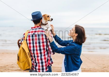 Young female and male tourists have walk near sea, carry their favourite pet, enjoy nice weather. Unrecognizable young male in checkered shirt carries bag and dog on hands, stands back at camera
