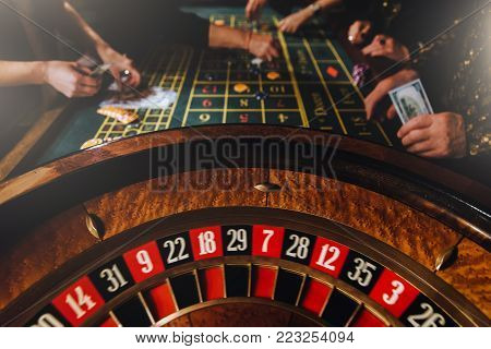 Casino theme. Pocker game. Unrecognizable gamblers play casino on money. Pocker cards and chips. Casino wheel and people in background. Upper class friends.