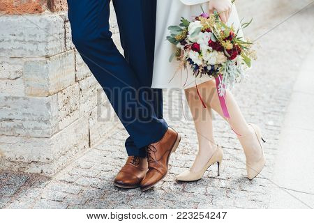 Cropped shot of beautiful bride on high heeled white shoes holds nice bouquete stands near groom who wears formal festive suit, celebrate their wedding. Happy newlyweds. Wedding couple outdoor