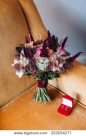 Wedding concept with bouquete and rings. Tender wedding bouquete and rings. Engagement rings. Beauty of colored flowers. Special event