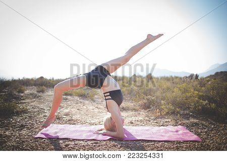 Female Model Practicing Yoga In The Outdoors Doing Stretching And Exercising Balance.