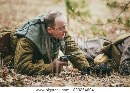 PRIBOR, BELARUS - April, 05, 2015: Unidentified re-enactor dressed as Soviet russian soldier lying on ground in forest