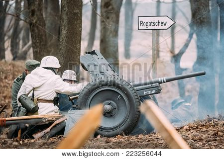 Rogachev, Belarus - February 25, 2017: Re-enactors Dressed As German Soldiers In WWII Load A Cannon Shells At Firing Position. Historical Reenactment