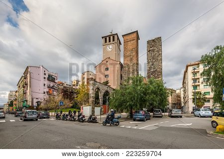 Savona, Italy - December 2, 2016: Street life and view of the Brandale Tower (The Torre del Brandale), Corsi and Riario minor towers in Savona, Liguria, Italy. This is the tower where the freedom declaration of Savona was signed in 1191.