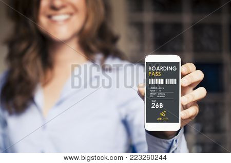 Boarding pass in a mobile phone screen. Close up of smiling woman hand holding the device.