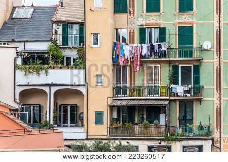 Savona, Italy - December 2, 2016: Laundry hanging out of a typical facade of a multistory residential building with clothesline ropes in Savona, Liguria, Italy.